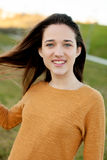 Outdoor portrait of beautiful happy teenager girl laughing. While the wind moves her hair Stock Photos