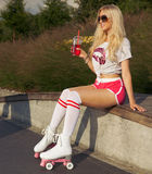 Outdoor Portrait Beautiful leggy long-haired young blonde woman in a vintage roller skates, sunglasses, T-shirt shorts sitting hot Royalty Free Stock Photo