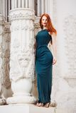 Outdoor portrait of beautiful redhead young woman. Near column royalty free stock images