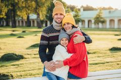 Outdoor portrait of beautiful smiling woman, handsome man and their little cute daughter stand together against ancient bilduing i stock photography