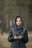 Outdoor portrait of beautiful thoughtful young woman wearing coat with hood texting on her smartphone posing in forest spring park. Outdoor portrait of beautiful Royalty Free Stock Images