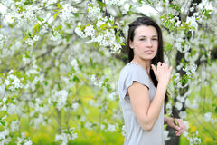Outdoor portrait of a beautiful woman in blooming tree in spring Royalty Free Stock Photography