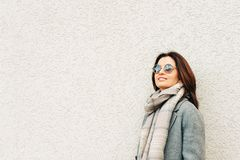 Outdoor portrait of beautiful woman wearing grey coat. Warm scarf and sunglasses with blue sky clouds reflection stock photography