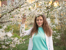 Outdoor portrait of a beautiful woman in white jacket among white blossom tree Royalty Free Stock Images
