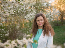 Outdoor portrait of a beautiful woman in white jacket among white blossom tree Royalty Free Stock Photos