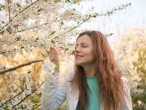 Outdoor portrait of a beautiful woman in white jacket among white blossom tree Royalty Free Stock Photo