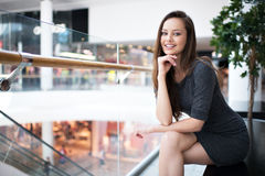 Outdoor portrait of the beautiful young happy woman. Attractive caucasian girl smiling and posing in the shop. Pretty female person with positive emotions royalty free stock images