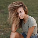 Outdoor portrait of a beautiful young stylish woman with curly stock images