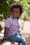 Outdoor portrait of a black baby sited on a bench Royalty Free Stock Images