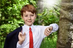 Outdoor portrait of boy going to First Holy Communion. Outdoor portrait of young boy in dark suit going to First Holy Communion stock photography