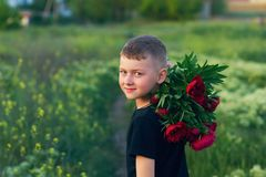 Outdoor portrait of a boy on a walk with peony flowers royalty free stock photography