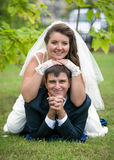 Outdoor portrait of bride lying on grooms back on grass at park Royalty Free Stock Photography