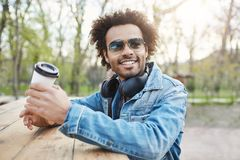 Outdoor portrait of charming stylish dark-skinned male with afro hairstyle, wearing trendy glasses and denim coat while royalty free stock photo