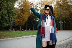 Outdoor portrait cheerful and stylish hipster girl in hat using royalty free stock photo