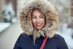 Outdoor portrait of cheerful woman. Wearing winter jacket with warm hood stock photography