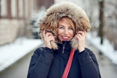 Outdoor portrait of cheerful woman. Wearing winter jacket with warm hood stock image