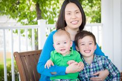 Outdoor Portrait of A Chinese Mother with Her Two Mixed Race Chi stock photo