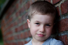 Outdoor portrait of cute boy. Portrait of cute boy near brick wall Royalty Free Stock Image