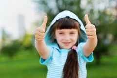 Outdoor portrait of cute child girl with thumbs up Royalty Free Stock Photos