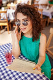 Outdoor portrait of cute curly girl in sunglasses having a drink in the cafe Stock Photos