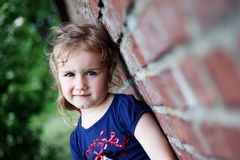Outdoor portrait of cute girl. Portrait of cute girl near brick wall Stock Photo