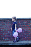 Outdoor portrait of cute girl. Portrait of cute girl near brick wall with pink balloons Royalty Free Stock Photos