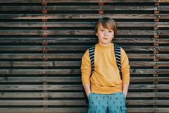 Outdoor portrait of cute kid boy. Wearing yellow sweatshirt and backpack. Back to school concept Royalty Free Stock Image