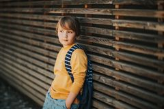 Outdoor portrait of cute kid boy. Wearing yellow sweatshirt and backpack. Back to school concept Stock Images