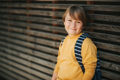 Outdoor portrait of cute kid boy. Wearing yellow sweatshirt and backpack. Back to school concept Royalty Free Stock Images