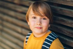Outdoor portrait of cute kid boy. Wearing yellow sweatshirt and backpack. Back to school concept Stock Image