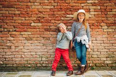 Outdoor portrait of cute little boy and girl. Stylish kids posing against vintage brick wall. Fashion for small children Royalty Free Stock Photo