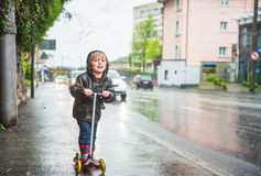 Outdoor portrait of a cute little boy. Cute little boy in a very wet clothes on the scooter next to road under the rain Royalty Free Stock Photo
