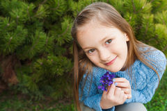 Outdoor portrait of a cute little girl. Close up portrait of a cute little girl, holding small bouquet of violets, wearing blue pullover Royalty Free Stock Photography