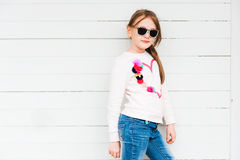 Outdoor portrait of a cute little girl. Fashion portrait of a cute little girl against white background, wearing sweatshirt and jeans Royalty Free Stock Photo