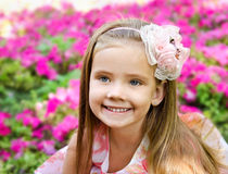 Outdoor portrait of cute little girl near the flowers Stock Photography