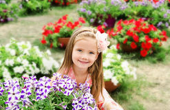 Outdoor portrait of cute little girl near the flowers Stock Image