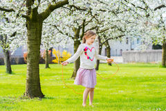 Outdoor portrait of a cute little girl. Pretty little girl playing in a spring garden on a nice sunny day, jumping with skipping rope, wearing sweatdhirt with a Royalty Free Stock Photography