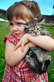 Outdoor portrait of a cute little girl with small kitten, girl playing with cat on natural background Stock Images