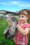 Outdoor portrait of a cute little girl with small kitten, girl playing with cat on natural background Royalty Free Stock Photography