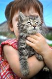 Outdoor portrait of a cute little girl with small kitten, girl playing with cat on natural background Royalty Free Stock Photo