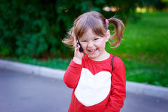 Outdoor portrait of cute little girl speaking by phone Stock Photos