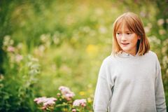 Outdoor fashion portrait of cute preteen girl. Outdoor portrait of cute little girl wearing grey pullover, enjoying nice day in sunny park Royalty Free Stock Image