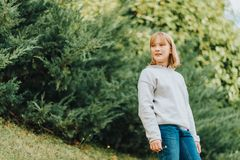 Outdoor fashion portrait of cute preteen girl. Outdoor portrait of cute little girl wearing grey pullover, enjoying nice day in sunny park Royalty Free Stock Images