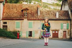 Portrait of little girl. Outdoor portrait of a cute little girl wearing schoolwear, holding beautiful bouquet of autumn flowers Royalty Free Stock Images