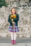 Portrait of little girl. Outdoor portrait of a cute little girl wearing schoolwear, holding beautiful bouquet of autumn flowers Stock Images