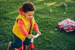 Outdoor portrait of cute little toddler boy. Playing in the park on a nice sunny day, wearing orange hoody jacket and yellow vest Royalty Free Stock Photos