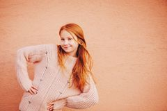 Outdoor portrait of cute preteen girl. Outdoor portrait of adorable red-haired preteen girl wearing soft pink pullover, kid model posing against beige wall Royalty Free Stock Images