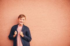 Outdoor portrait of cute preteen girl. Outdoor portrait of adorable preteen girl wearing soft pink dress and purple cardigan, kid model posing against beige wall Royalty Free Stock Photo