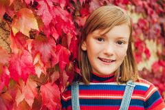 Outdoor portrait of cute preteen girl. Outdoor close up portrait of adorable preteen girl of 10 years old, leaning on red ivy wall Royalty Free Stock Photo
