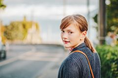 Outdoor portrait of cute preteen girl. Looking over the shoulder, wearing purple knitted jacket Stock Photo